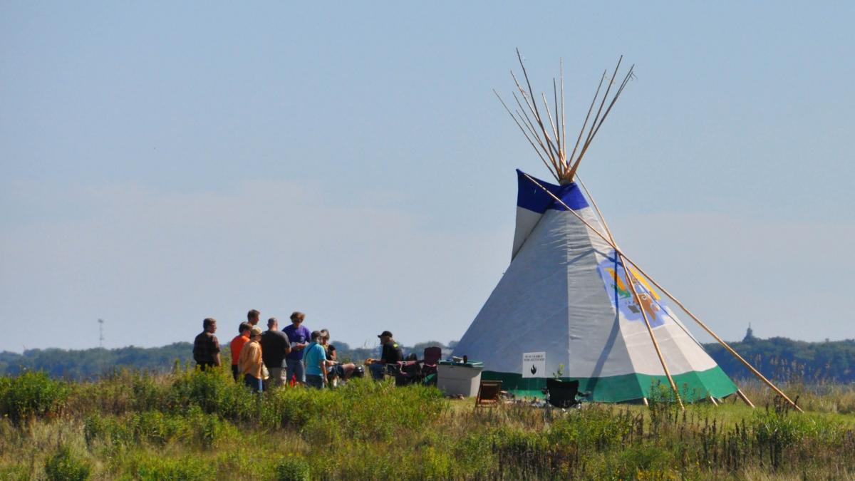 students standing alongside a tepee